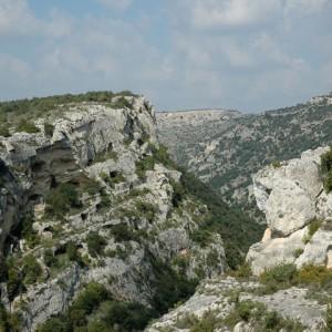 sei-su-immagine-raffigurante-veduta-delle-grotte-di-cozzica-scavate-nel-fianco-del-canyon-detto-gravina-di-materasasso-barisano-e-cattedrale-di-matera