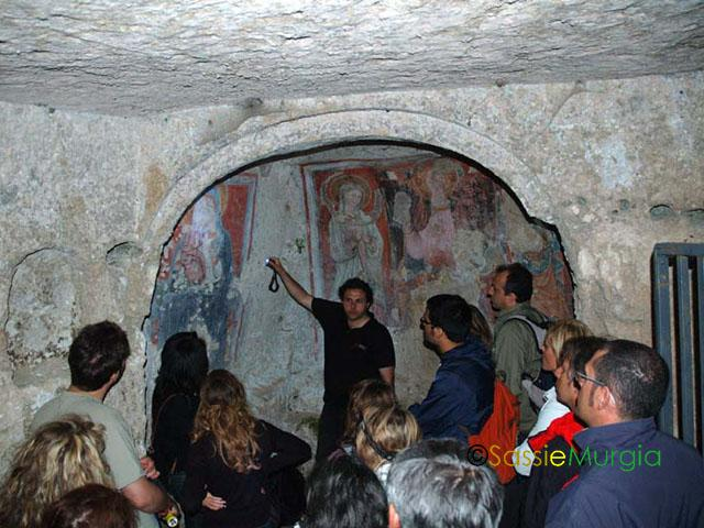 sei-su-immagine-raffigurante-Francesco-mentre-spiega-l-affresco-riproducente-la-Madonna-del-Melograno-nella-chiesa-rupestre-della-madonna-delle-tre-porte