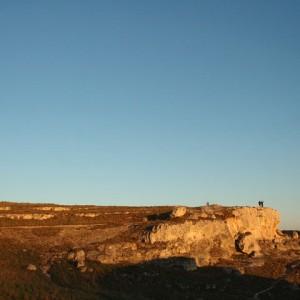 sei-su-immagine-raffigurante-un-tramonto-estivo-tinge-di-arancio-una-rupe-della-gravina-di-matera