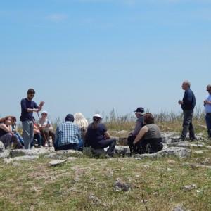 sei-su-immagine-raffigurante-luca-mentre-spiega-il-villaggio-neolitico-di-murgia-timone-ad-un-gruppo-di-persone-con-disabilità-psichica